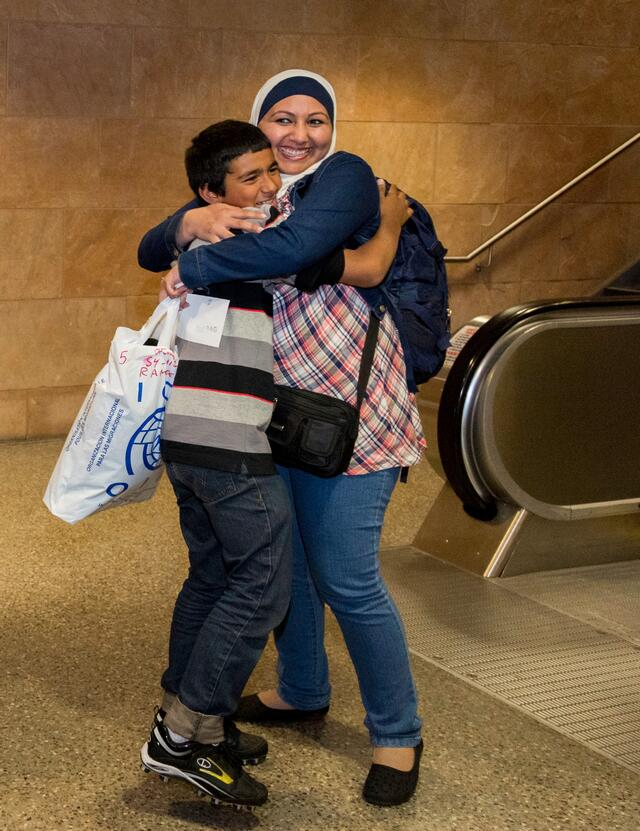 A refugee family hugs, smiling as they are reunited in a U.S. airport.