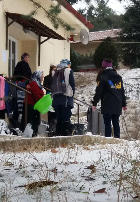 IRC aid workers speak with refugees outside a building in the Veria refugee site in northern Greece after a snowfall.