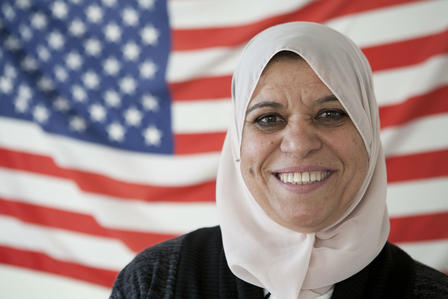 Bushra Naji stands before an American flag
