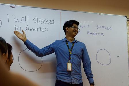 "Fadzil Imran Bin Ismail, an RSC cultural orientation trainer, shows his students writing on a whiteboard that reads, ""I will succeed in America."""