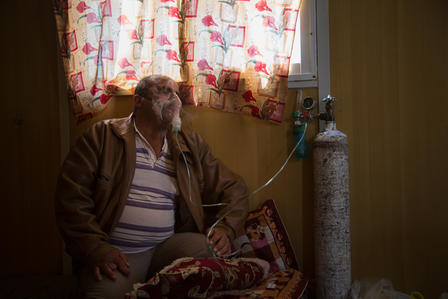 Abu Raed sits by a window in his caravan, wearing an oxygen mask.