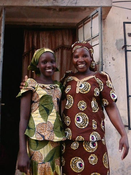 Ruth stands with her mother outside their home in Yola.