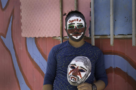 A young Syrian refugee wears and carries masks he painted at an IRC workshop