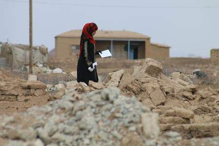 A woman picks her way through the rubble of her village in northeastern Syria.