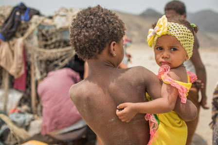 A young boy displaced by the civil war in Yemen stands with his baby sister outside a makeshift shelter