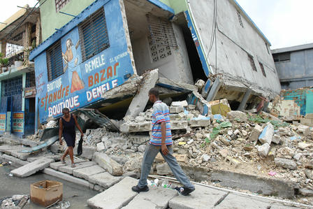 People walk past earthquake-damaged buildings in Port-au-Prince, Haiti in 2010