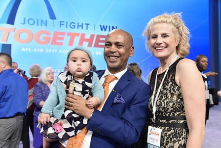 Tefere Gebre stands with his wife and holds his baby daughter