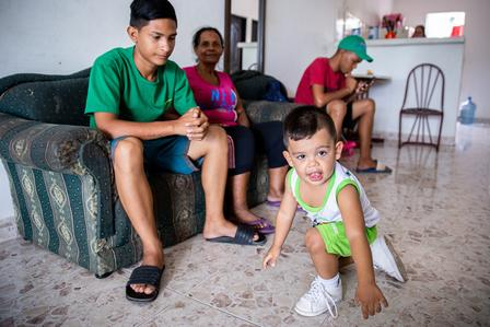 Cibel's youngest son, Matías, plays at home with his cousin, aunt and older brother nearby.