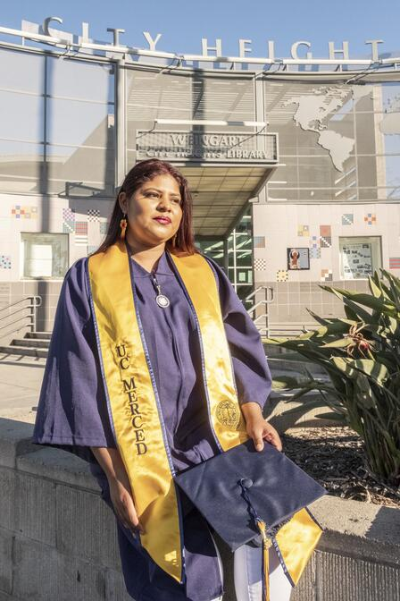 DACA recipient Lupe wearing her UC, Merced college graduation robes outside a building in her San Diego neighborhood