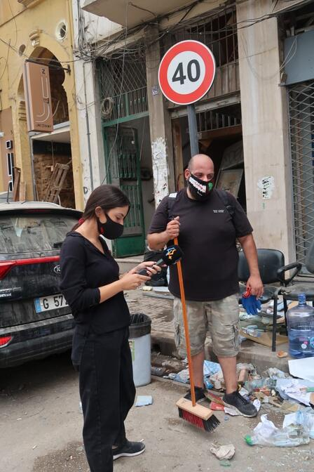 Elias El Beam holds a broom while another volunteer checks her phone as they help clear debris after the Beirut explosion