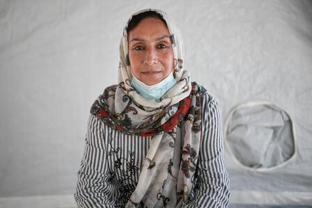 Rahima sits inside a tent in the refugee camp where her family lives in Lesbos, Greece