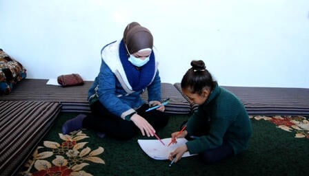 IRC counselor Fadia and 8-year-old Reem sit on a carpet looking at Reem's drawing pad.