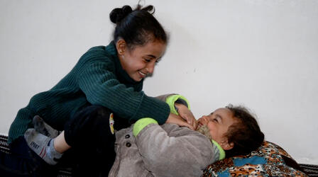 8-year-old Reem, smiling, plays with her giggling little sister Layla in Syria.