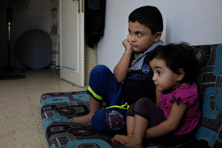 Two Syrian children watch cartoons