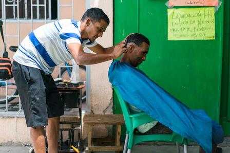 Antonio gives a man a haircut