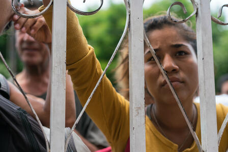 A woman in a group of Colombians and Venezuelans waiting outside a soup kitchen
