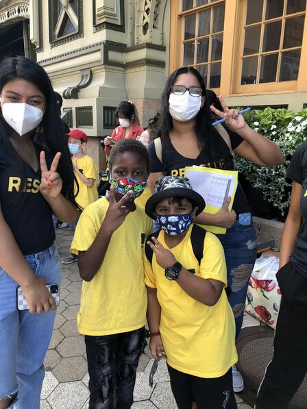 Two peer mentors and two lower school students smiling and posing with a peace sign. All four are wearing masks. The peer mentors wear a black rescue t-shirt and the two lower school students wear a yellow shirt with the IRC logo.