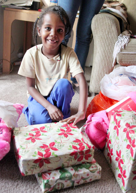 A refugee child opens a present