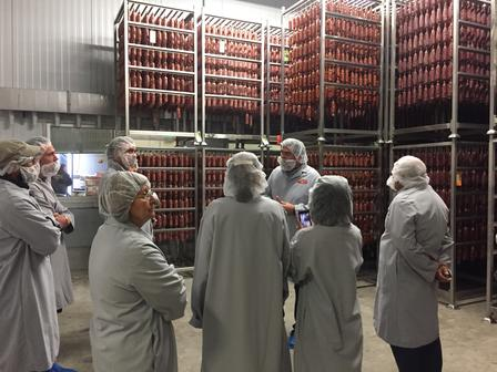 Spice Kitchen, a program of the International Rescue Committee, entrepreneurs and staff take a tour of Creminelli Fine Meat's facilities.