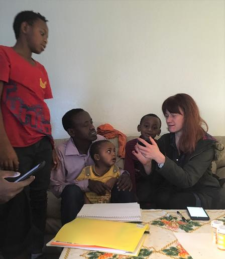 Erica, a health mentor with the International Rescue Committee in Salt Lake City, uses her phone as a translator to communicate with the family she mentors.