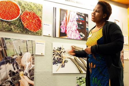 African women stands in front of photos of food and livestock