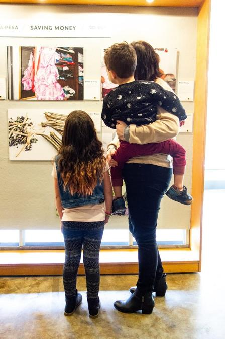 Women holds young child and stands with other child, all looking at photos