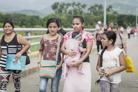 Women and children walk across the bridge between Venezuela and the city of Cucuta, Colombia.