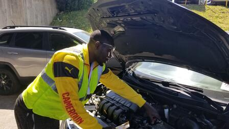 """Norbert works on a car at his auto shop in Stone Mountain. He is wearing a sweater that has """"Cameroon"""" printed on the sleeve."""