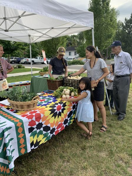 Customers enjoy freshly grown, culturally appropriate produce grown by New Roots farmers. New Roots is a program of the International Rescue Committee in Salt Lake City.