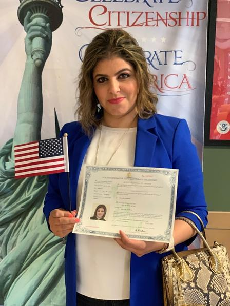 Lina holding her citizenship certificate and an American flag after she was sworn in as a US citizen.
