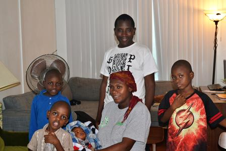 Elie and his family, resettled by the International Rescue Committee, stand in their living room in Salt Lake City