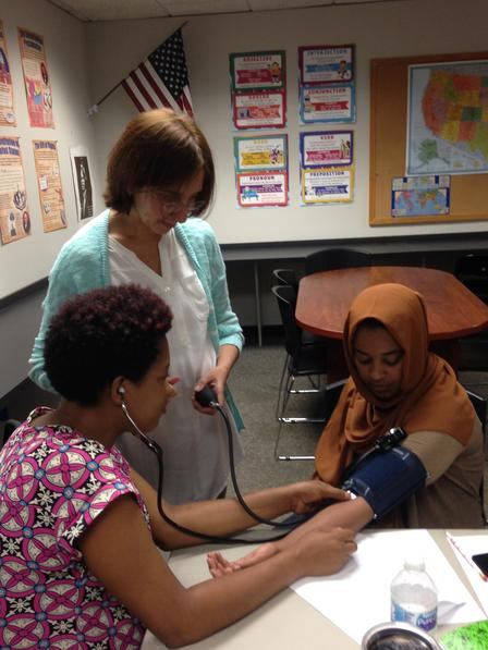 Class participants work with the CNA instructor to check each others blood pressure.