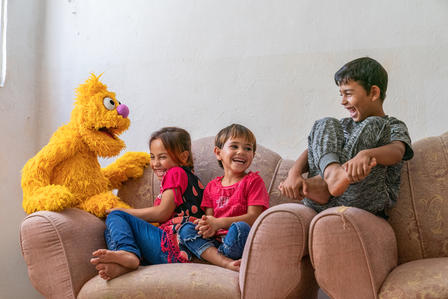 Jad, a furry Muppet character from the new Sesame Street show for refugees, Ahlan Simsim, with three laughing Syrian children