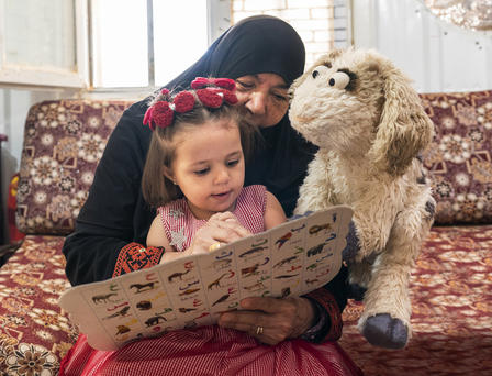 Ma'zooza, a baby goat Muppet on 'Ahlan Simsim', reads along with a young Syrian child and her caregiver in Azraq refugee camp in Jordan.