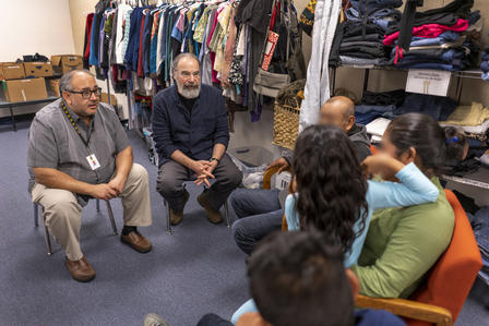 Mandy Patinkin speaks with a family who fled from Mexico at IRC welcome center in Phoenix, Arizona