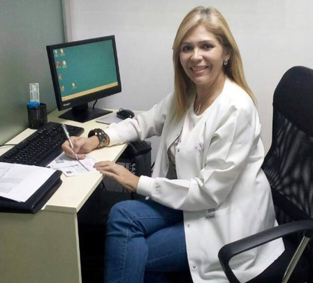 Dr. Edna Patricia Gomez poses at her desk in front of a computer in the IRC sexual and reproductive health care in Cúcuta, Colombia.