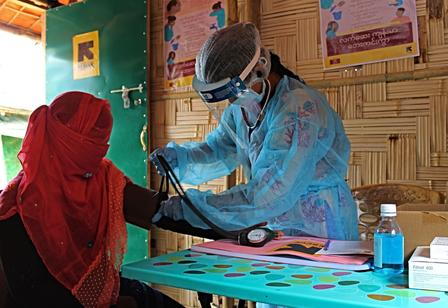 Wearing full PPE, including a face shield, a midwife takes the blood pressure of a patient.