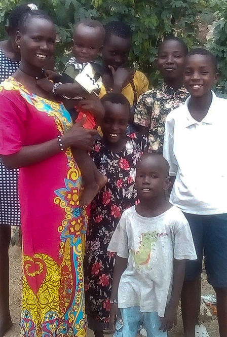 Florence Lokitoe poses with her children. They are standing outside and she is holding a baby, while five children stand next to her.