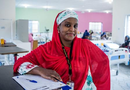 Dr Fatima poses with files at work wearing a red head scarf. There are hospital beds behind her.