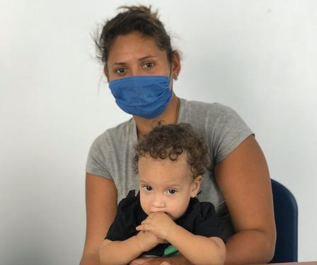 A woman wearing a mask sits with her child on her lap at an IRC-run clinic at the Simón Bolívar bridge.
