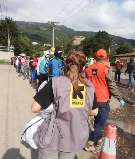 An IRC staff member stands with her back to the camera. In front of her is a line of people waiting to receive supplies.