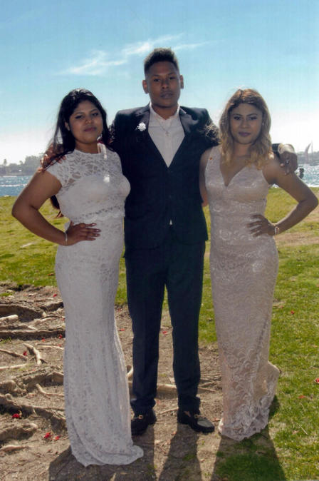 DACA recipients Lupe, her brother and sister pose for a photo with their arms around each other at a festive family event