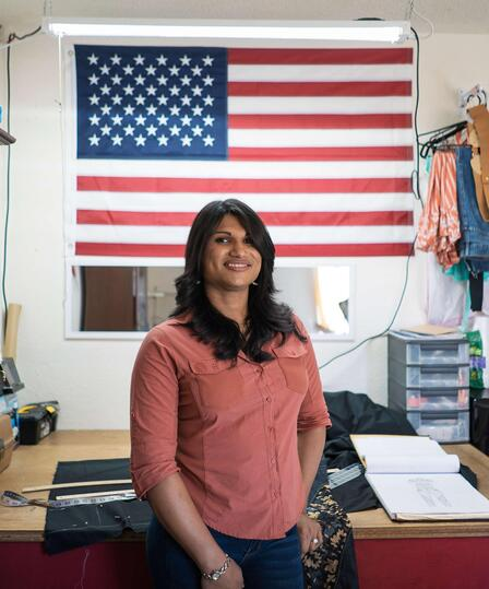Lincy Sopall stands in her studio for her fashion design business. She is wearing a pink button down shirt and smiling. Behind her is a desk, supplies for her work, and a large American flag.