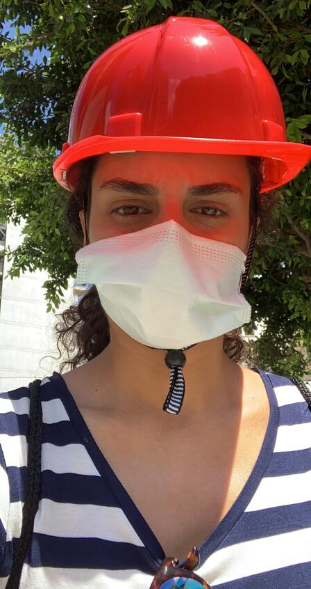 A selfie photo taken by Rebecca Mouawad. She is wearing a red hard hat and a white surgical mask.