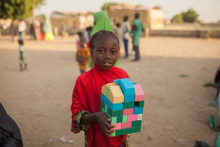 A child holds blocks at an IRC Safe healing and Learning Space in northeast Nigeria.