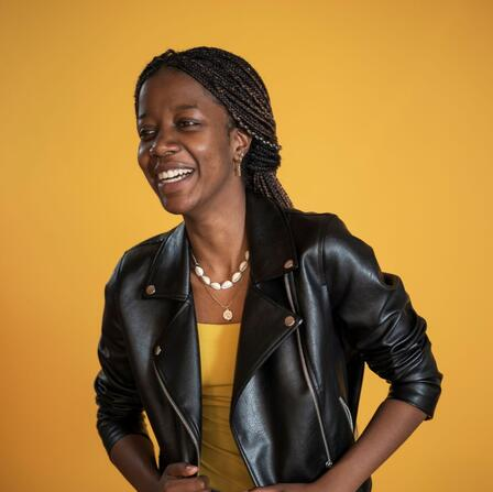 Christelle, wearing a black leather jacket, smiles and poses in front of a yellow background.