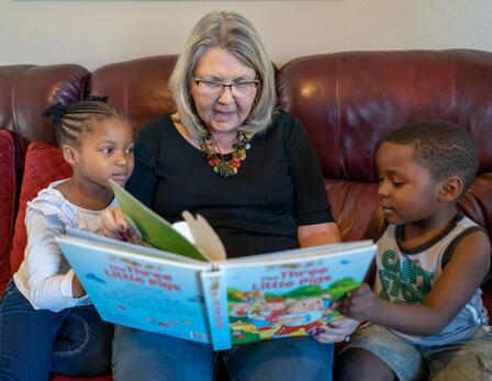 Julie Kurz reads to Sandra and Agape. They are sitting on a couch, the kids on either side of her with the book open on her lap.
