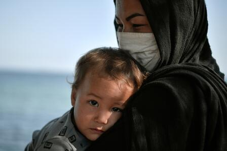 A mother wearing a face mask holds her baby in a refugee settlement in Greece