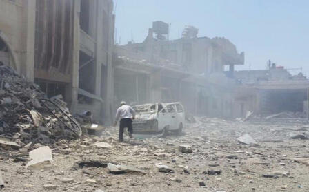 A man walks toward a crushed car in front of a recently bombed building. There is rubble and dust and smoke in the air.