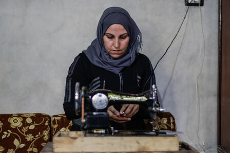 Um Abdo sits at a sewing machine to make COVID-19 masks in Syria